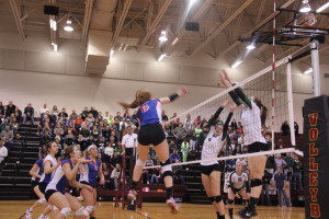 Junior Autumn Lockley goes up for a kill with the rest of the team ready to recover the block